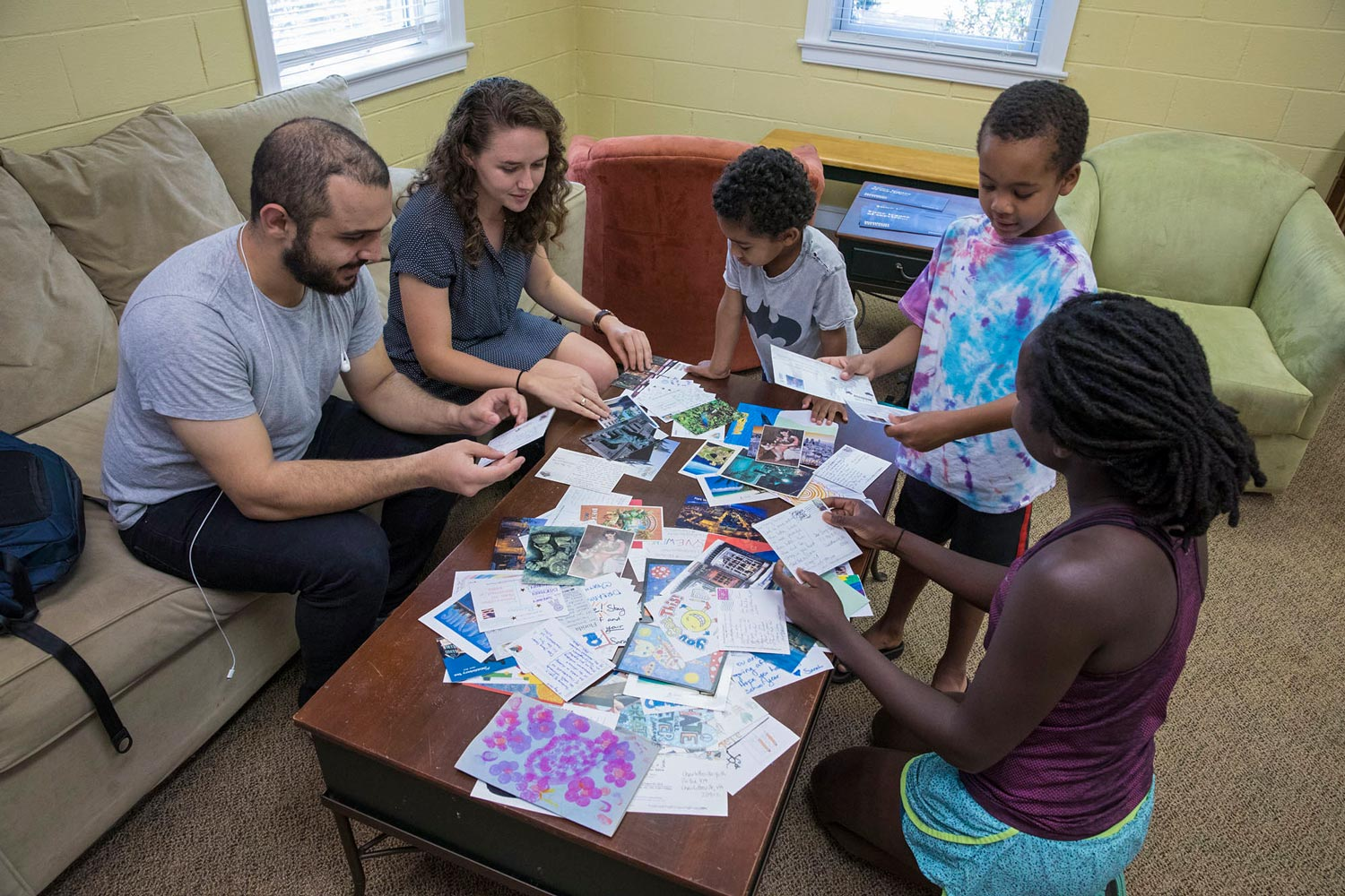 Madison House student board members Nojan Rostami and Margaret Haltom, seated on couch, show postcards to Abigail Kayser, a doctoral student in the Curry School of Education, and her two sons, Miles and Grant.