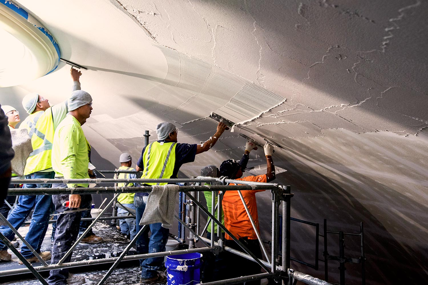 Employees of Interior Specialty Construction, Inc. of Providence Forge, slather plaster on the ceiling of the Rotunda's Dome Room.