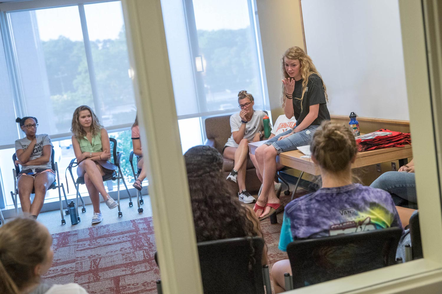 Students listen to resident adviser Rebecca Lewis last August in a meeting room on the third floor of Lile-Maupin House. (Photo by Sanjay Suchak, University Communications)