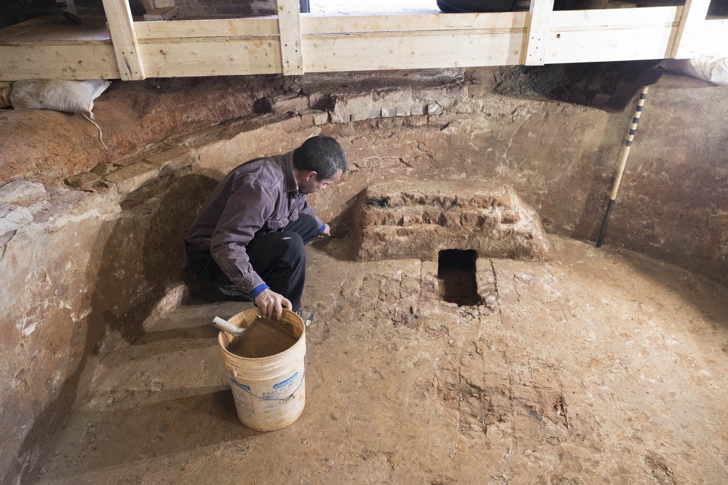 Archaeologist Ben Ford, of Rivanna Archaeological Services, works on the cistern found underneath Lawn room 24.