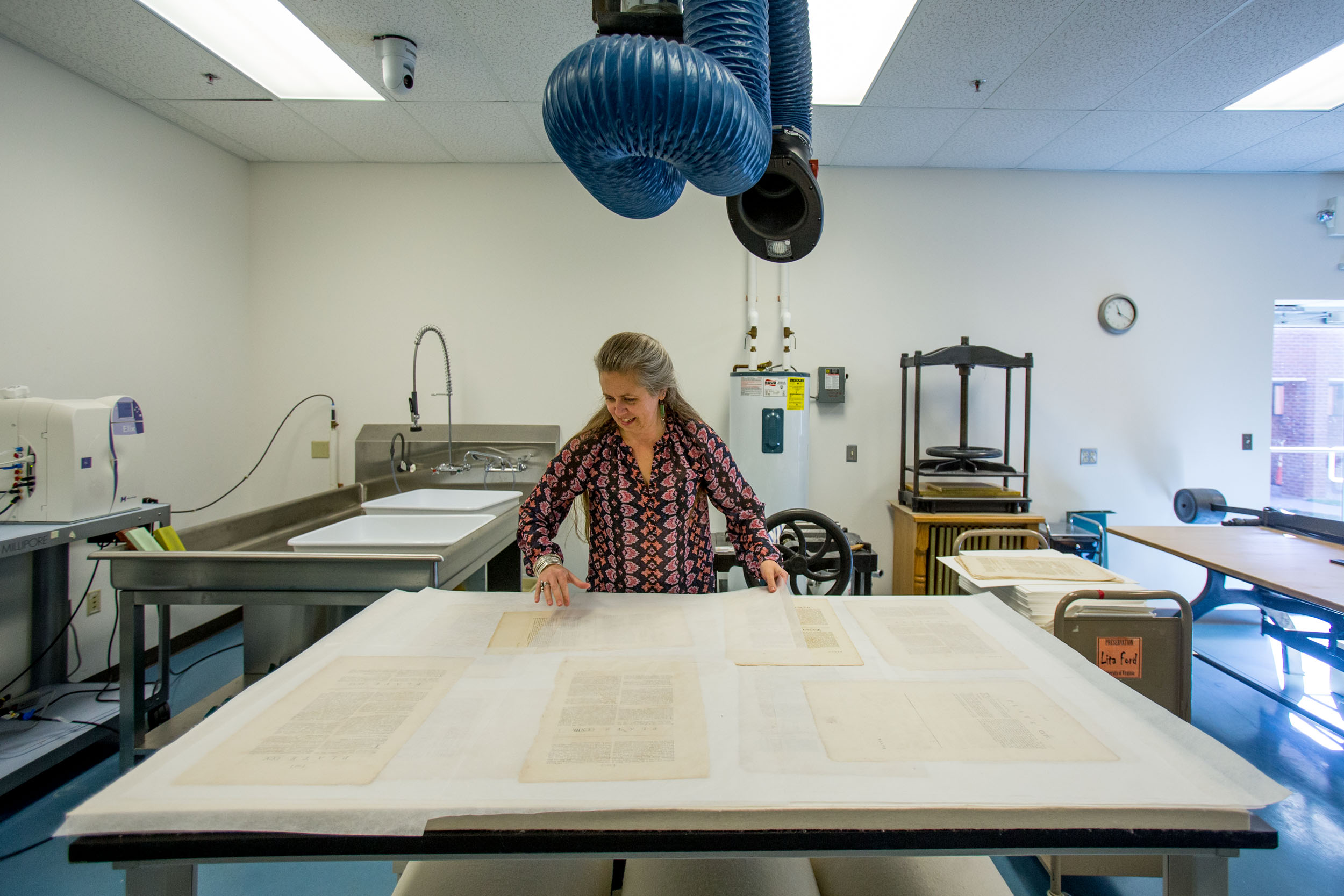 Gilligan lays out newly cleaned pages of Carter's original volume. Photos by Sanjay Suchak / University Communications
