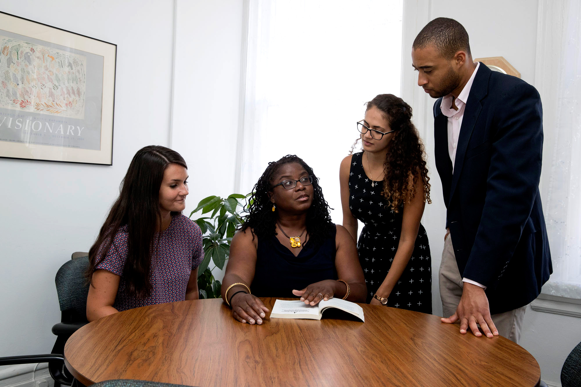 Jaronda Miller-Bryant (center, seated) works with interns, including Courtney Morgan, left, Kimia Nikseresht, and Luke Williams, Martin Luther King research assistant (both standing).