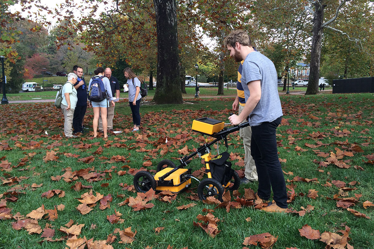 "Hutch Landfair, a student in ""Field Methods in Historic Preservation,"" uses ground-penetrating radar equipment to help identify foundations of now-missing buildings."