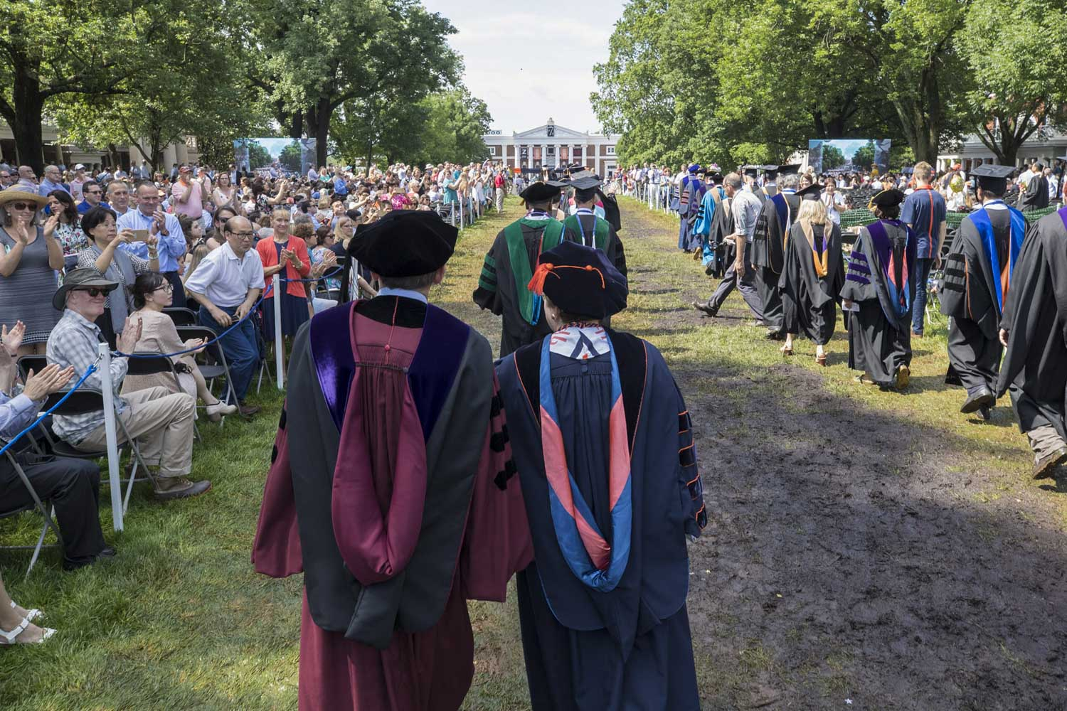 Faculty members walk around the muddy patches on the Lawn during Final Exercises.