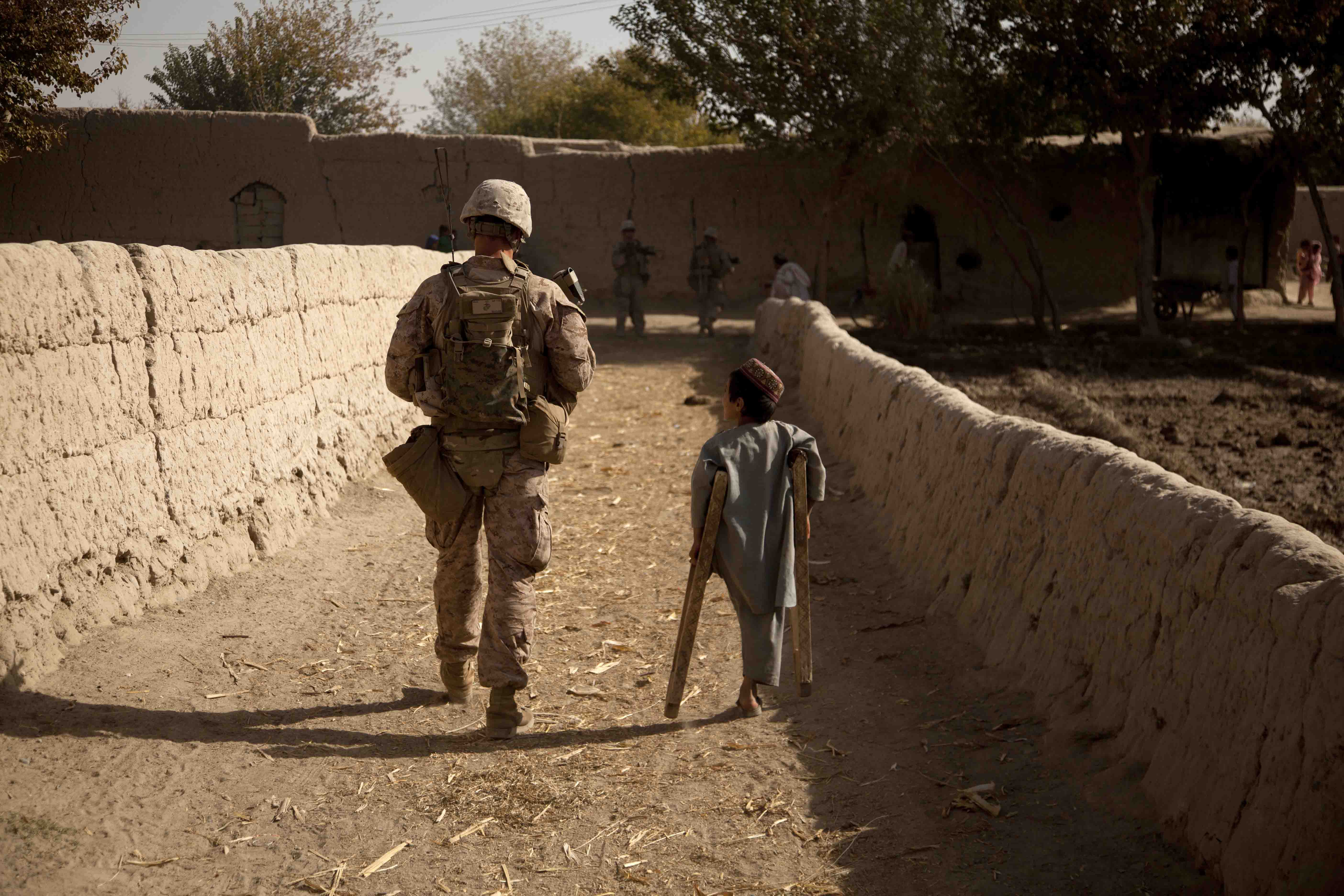 India Company's Cpl Jacob Marler patrols through the Southern Green Zone alongside one of the many Afghan children caught in the struggle between the Marines and the Taliban. (U.S. Marine Corps photo by LCpl Armando Mendoza)
