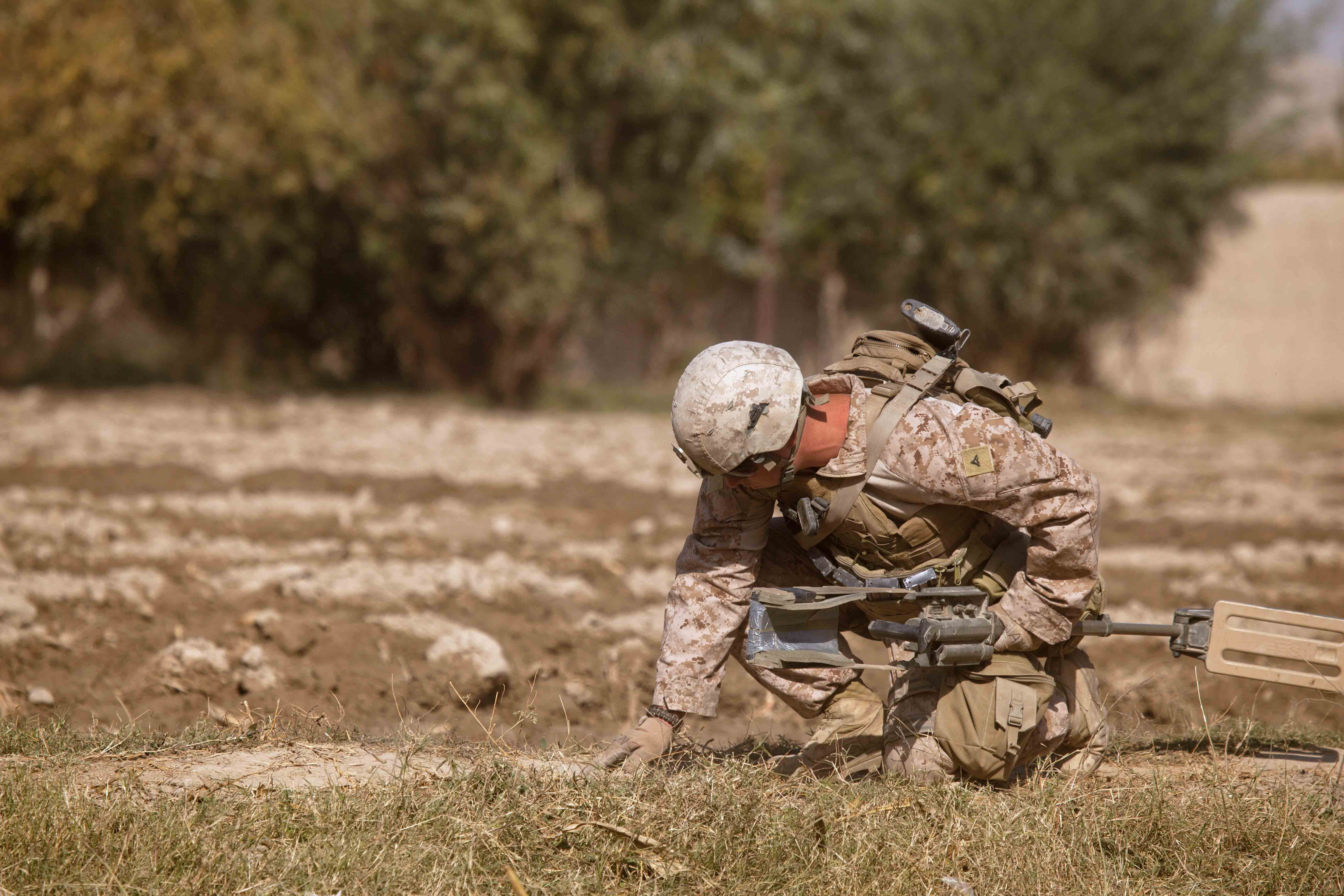 India Company's LCpl Sean Holloway pauses with his metal detector and probes for an IED while on patrol in the Southern Green Zone. (U.S. Marine Corps photo by LCpl Armando Mendoza)