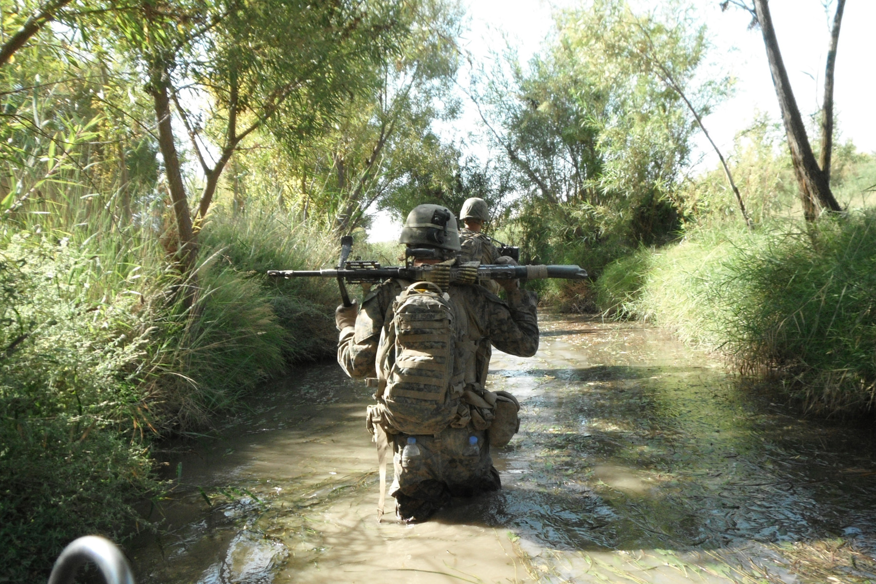 The safest, and least comfortable, route. Kilo Company's LCpl Casey Allison patrols with 1st Platoon through one of the Northern Green Zone's ubiquitous canals - the only place sure to be free of IEDs. (Photo courtesy of Seth Folsom.)