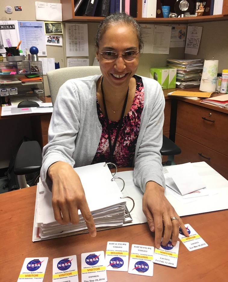 Francine Garrett-Bakelman with visitor passes she accumulated through her work at the Johnson Space Center in Houston. (Contributed photo)