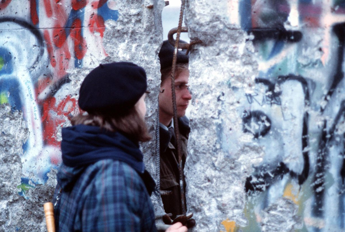 A West German girl speaks with an East German guard through an opening in the Berlin Wall in December 1989.