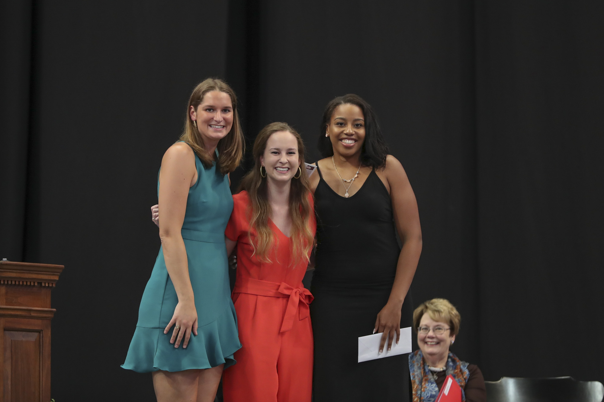 The Seven Society's Louis A. Onesty Memorial Scholar-Athlete Awards went to volleyball player Haley Fauntleroy, left, a public policy and leadership graduate, and basketball star Lauren Moses, an American studies graduate. Kirby Evett, center, presented.