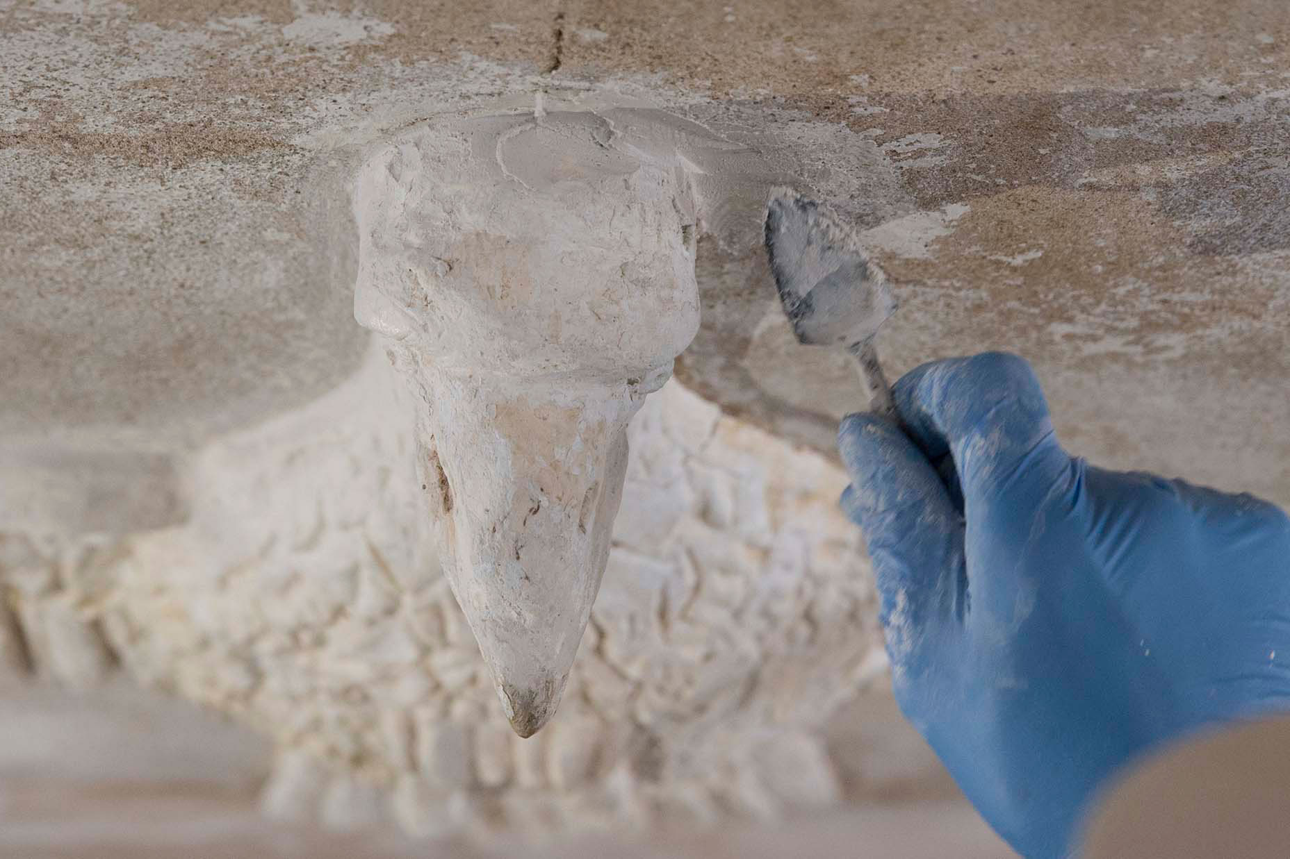 Master plasterer Noel Bird carefully repairs and preserves the eagle on the ceiling of the Rotunda's south portico.
