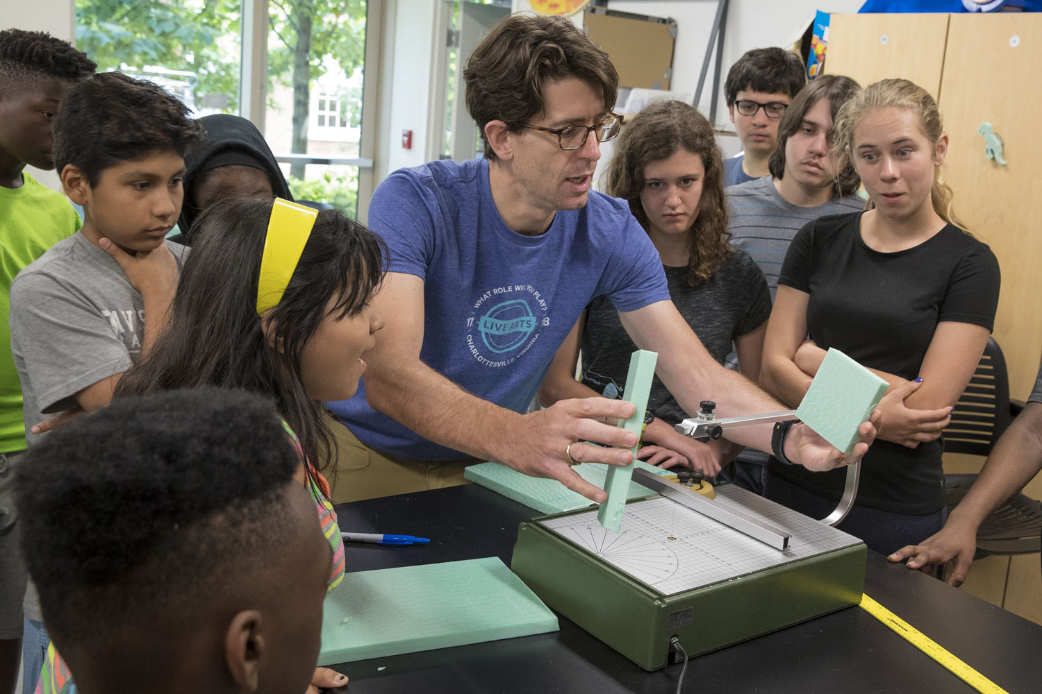 Reid Bailey, a UVA systems and information engineering professor who co-led a summer camp with Computers4Kids, shows youths how to slice foam board for the haunted house.