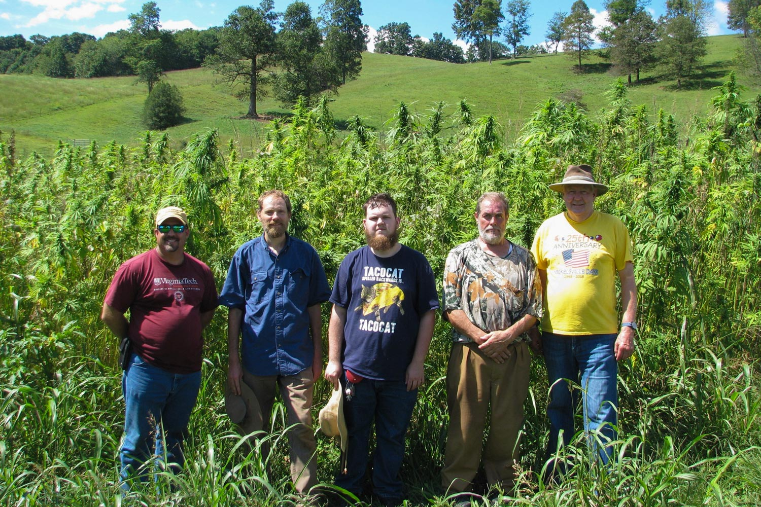Huish, second from the left, poses with area farmers in front of a stand of hemp.