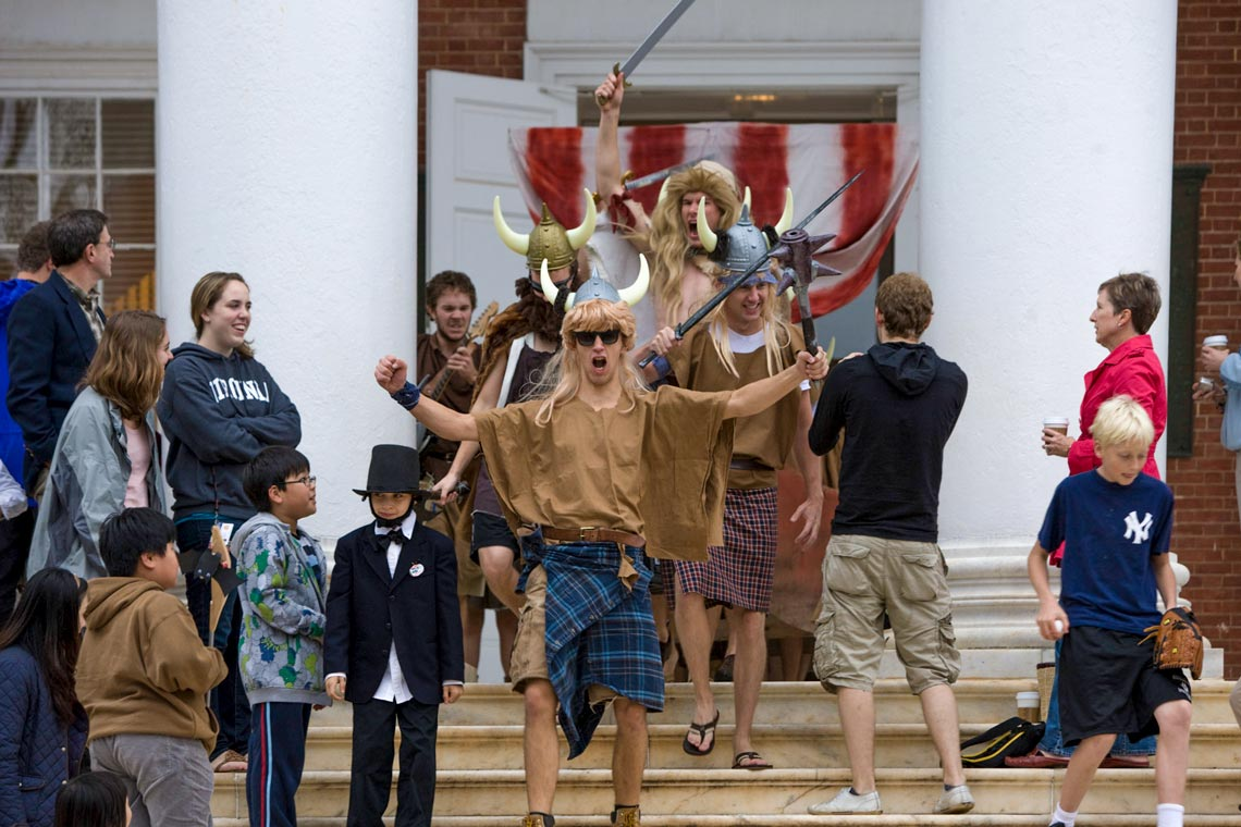 Several male college students dressed in viking costumes descend a staircase