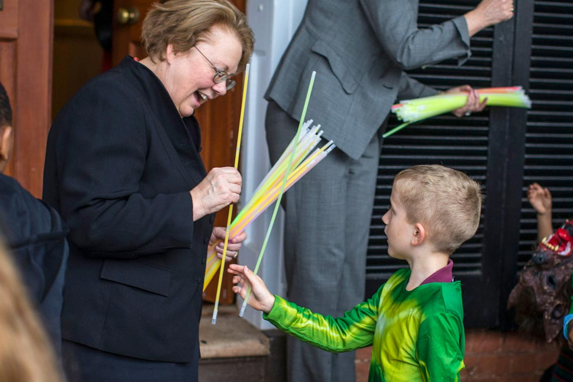 A smiling woman hands a glowstick to a little boy in a green costume