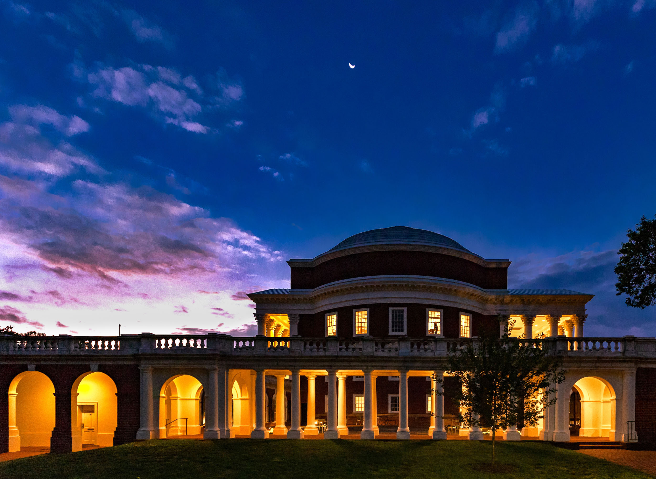 """The moon hangs above the Rotunda at sunrise, Crane's favorite time to photograph Grounds. """"The inky blue hour skies combined with the first hint of morning color make for a magnificent view,"""" he said. (Photo by Joshua Crane)"""