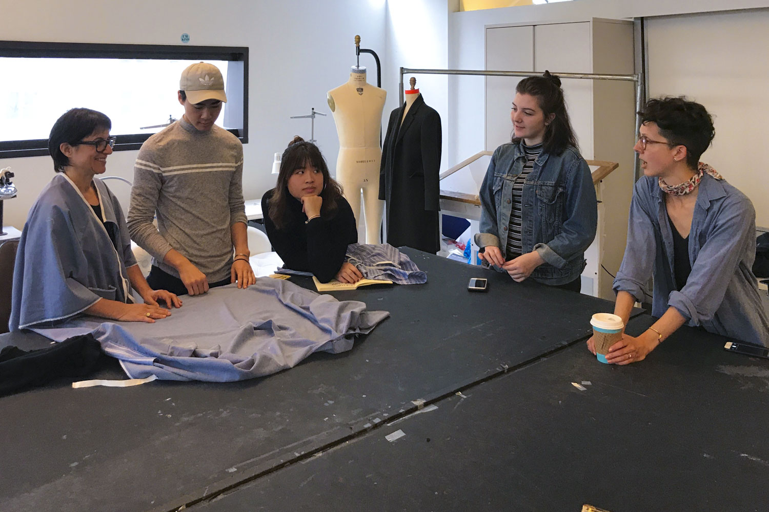 Care+Wear partnered with the Parsons School of Design to create the gowns. Here, teacher Brittany Dickinson, right, and her students talk with patient Joan DeCollibus, left, about a prototype gown.