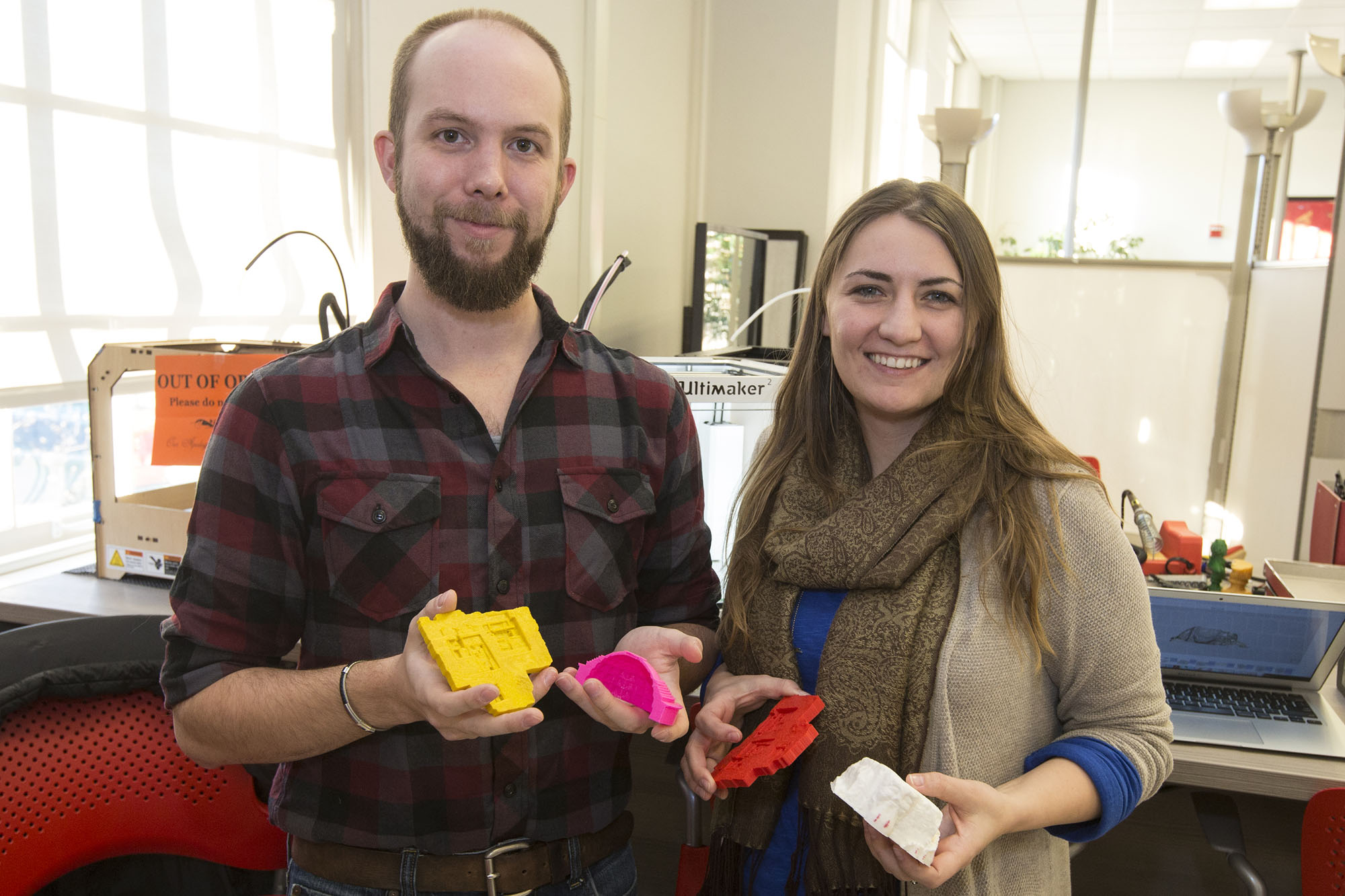 Graduate students Jennifer Grayburn and Benjamin Gorham hold examples of artifacts and archaeological dig sites they've recreated using the 3-D printer.