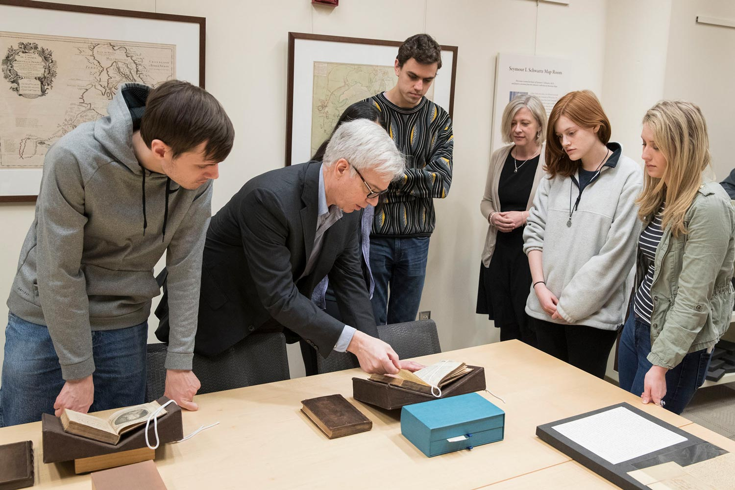 "O'Brien shows students several editions of Jonathan Swift's ""Gulliver's Travels."" Chris Ruotolo, third from right, and O'Brien received an NEH grant to digitize authoritative editions of online books."