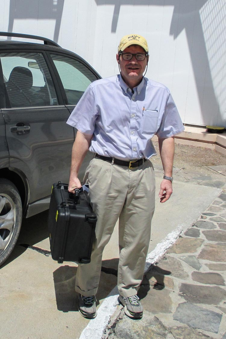 """Wilson at the the Las Campanas Observatory in Chile, holding the infrared detectors (that the team nicknamed """"the nuclear football"""") he'd carried with him all the way from Charlottesville."""
