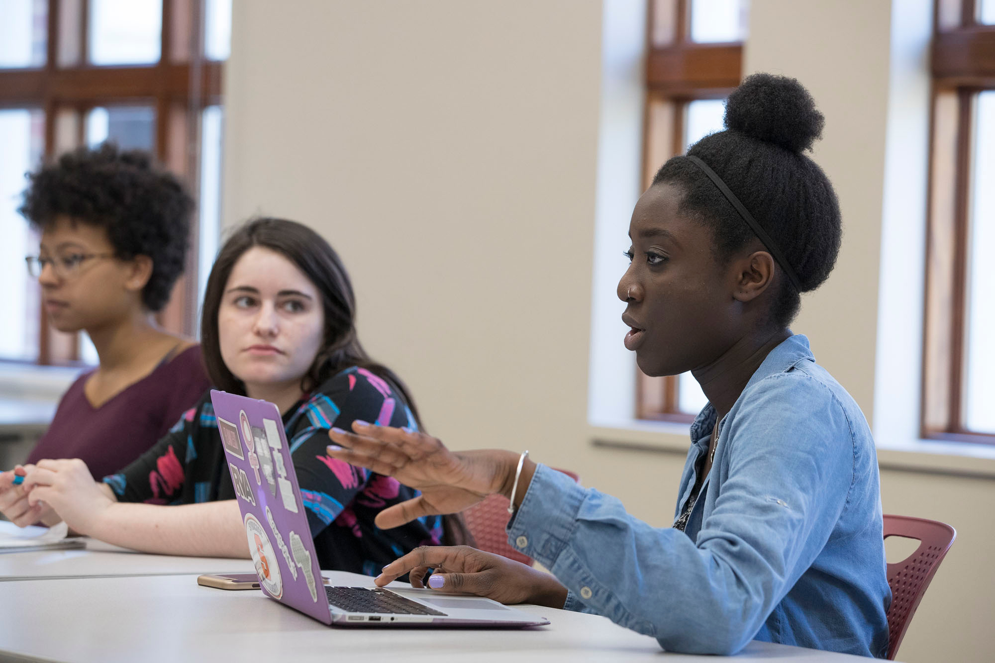 """Left to right, students Marrissa Jones, Taylor Campbell and Fota Sall discuss writing and community service in the seminar, """"Words Matter: Writing, Leadership and Community Engagement."""""""
