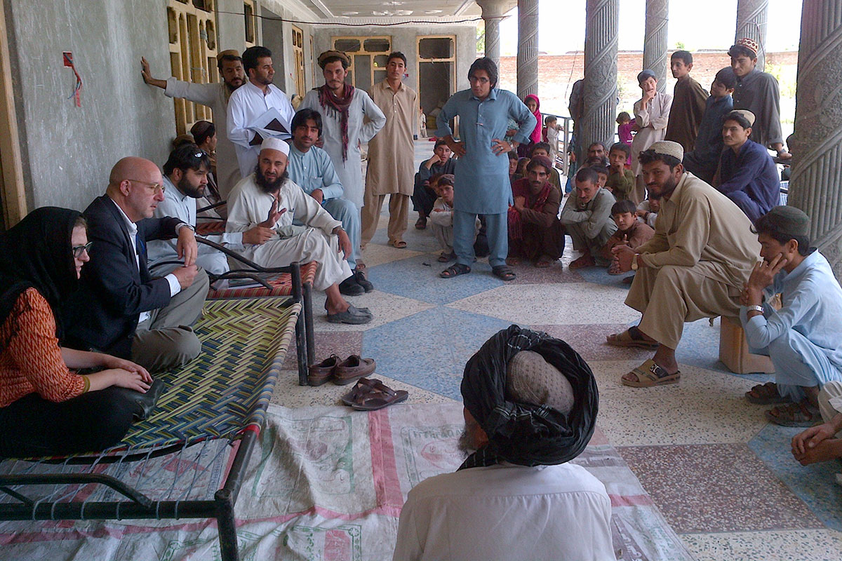 Danziger, second from left, meets with migrants and officials near the border of Afghanistan and Pakistan.