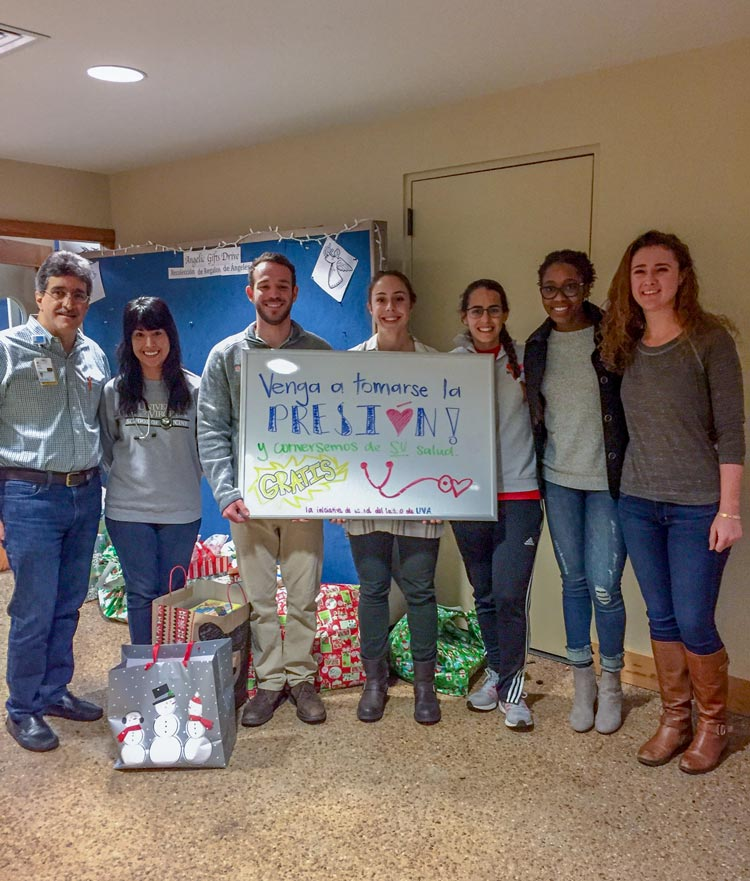 Luna welcomes patients to pop-up clinic at a local church. Pictured with him are medical students Janet Arras, Ralph Grauer, Tessa Klumpp, Elisa Enriquez Hesles, Edy Ndem and Katie Berry.