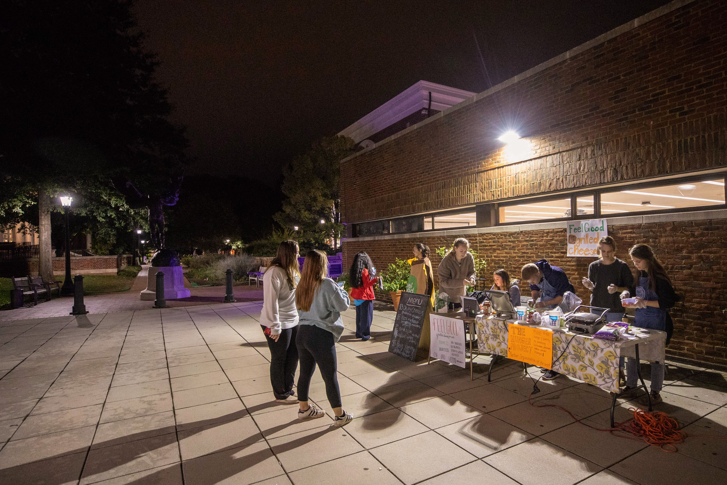 "Neal and fellow members of FeelGood holding a ""deli"" outside Clemons Library last fall."