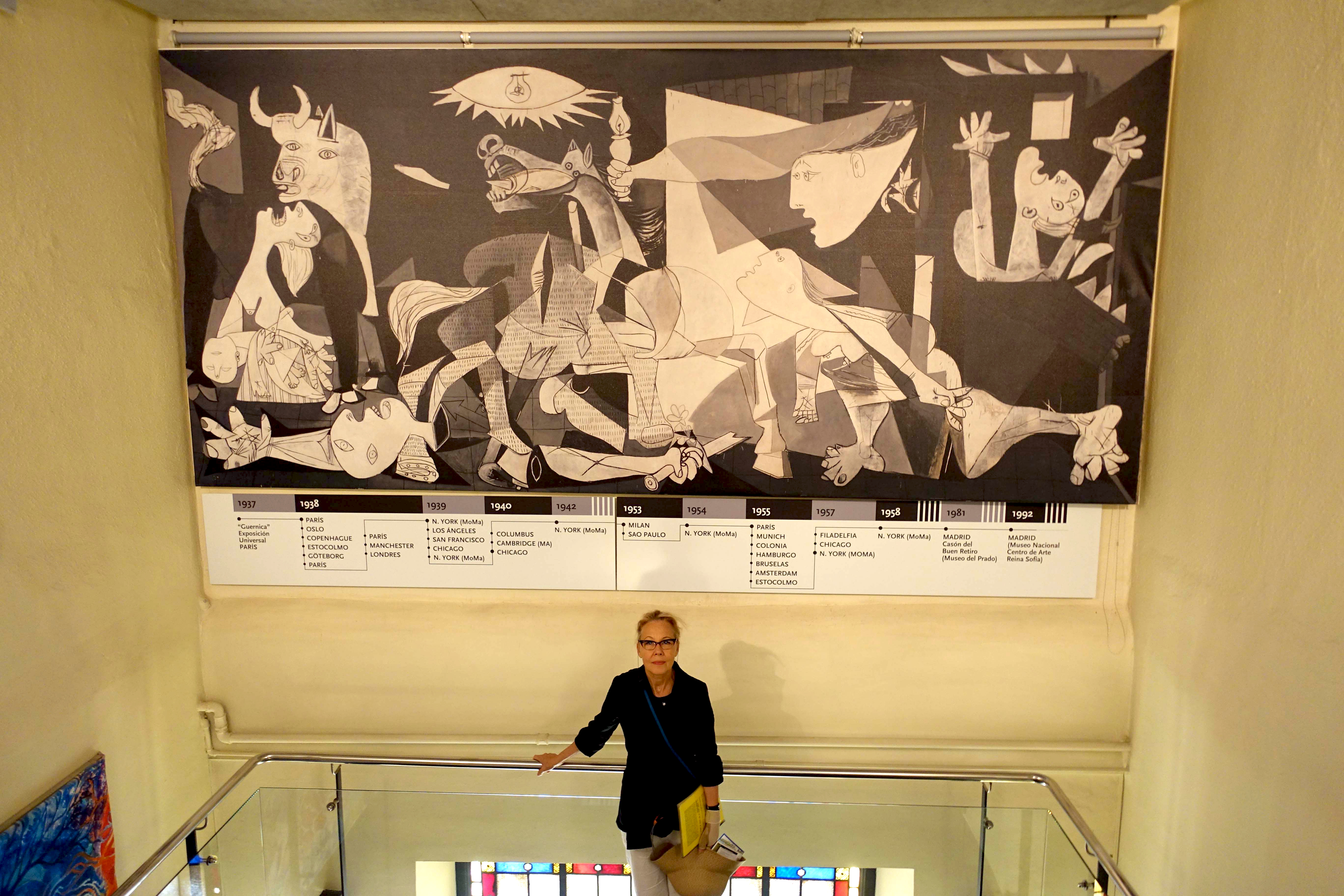 "McKinnon, at the Gernika Peace Museum in Spain, stands in front of a duplicated image of Picasso's ""Guernica"" showing a timeline of its exhibition history in Europe and the U.S. The museum is near the site of the Luftwaffe bombing that inspired Picasso's"