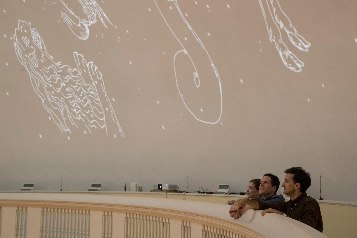 English Ph.D. candidates (from left) Madeline Zehnder, Neal Curtis and Samuel Lemley won a Jefferson Trust grant to recreate Jefferson's idea for a Rotunda Planetarium. One of the projectors is visible in the center of the photo.