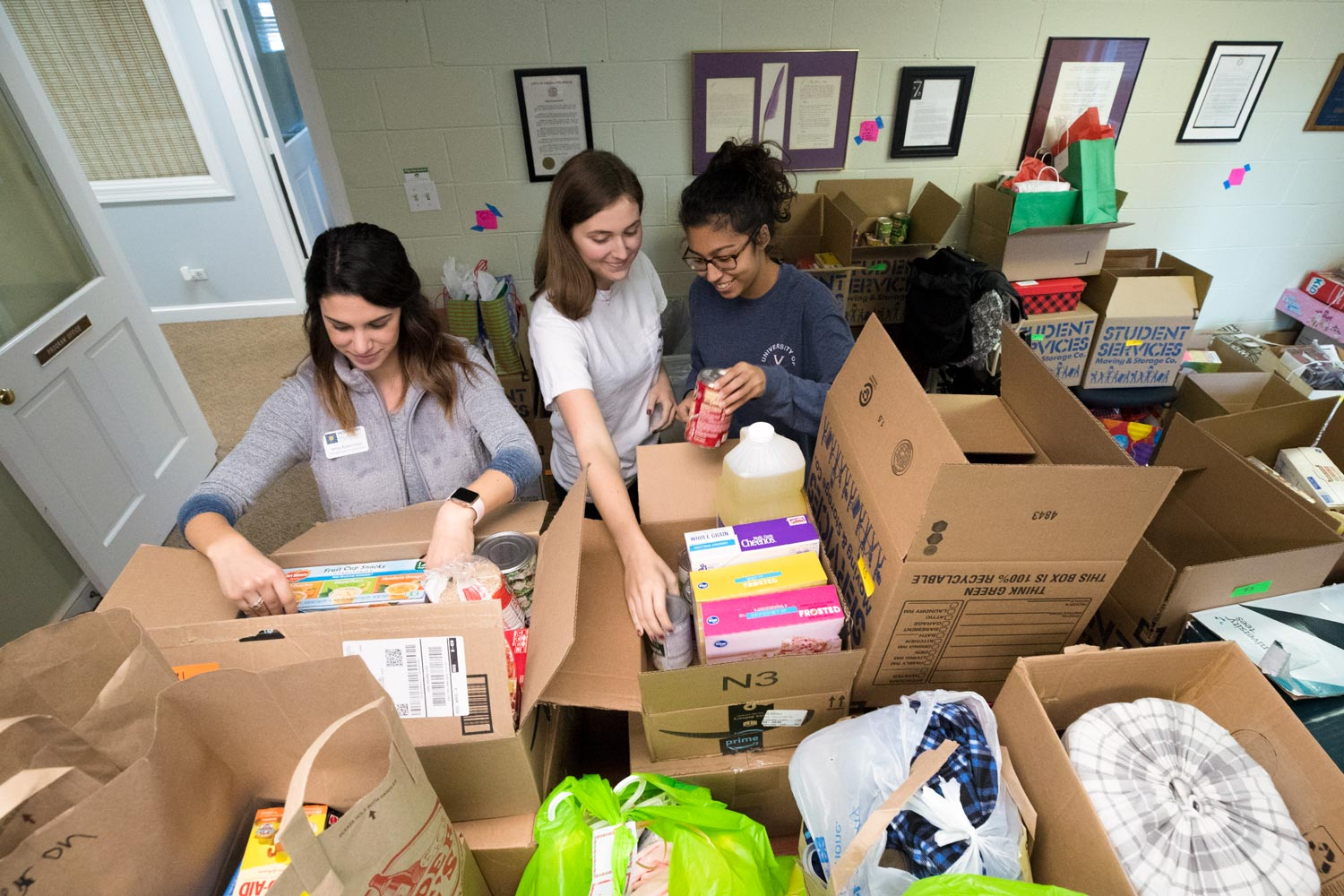 Madison House student volunteers with the Holiday Sharing program (from left) Amy Ackerman, Ally Bollettino and Salwa Malik organize boxes of food and gift for local families in need.