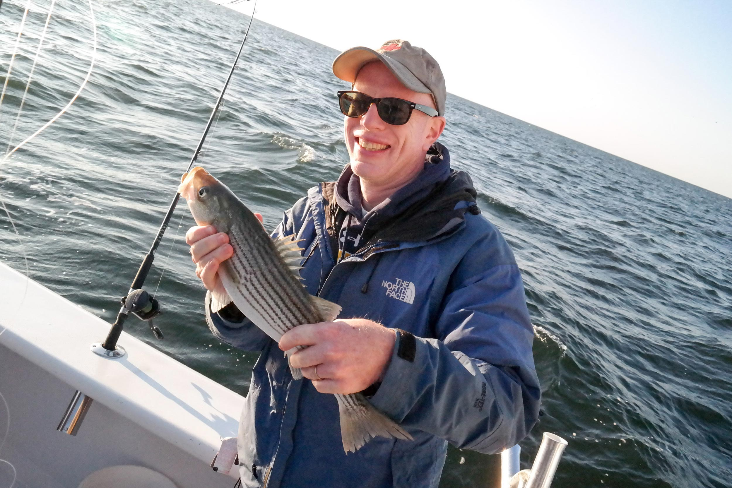 Peter Hedlund, director of Encyclopedia Virginia, took this photo of Mark Saunders in 2015 after he caught a striped bass, or rockfish, on their annual fishing trip in the Chesapeake Bay.