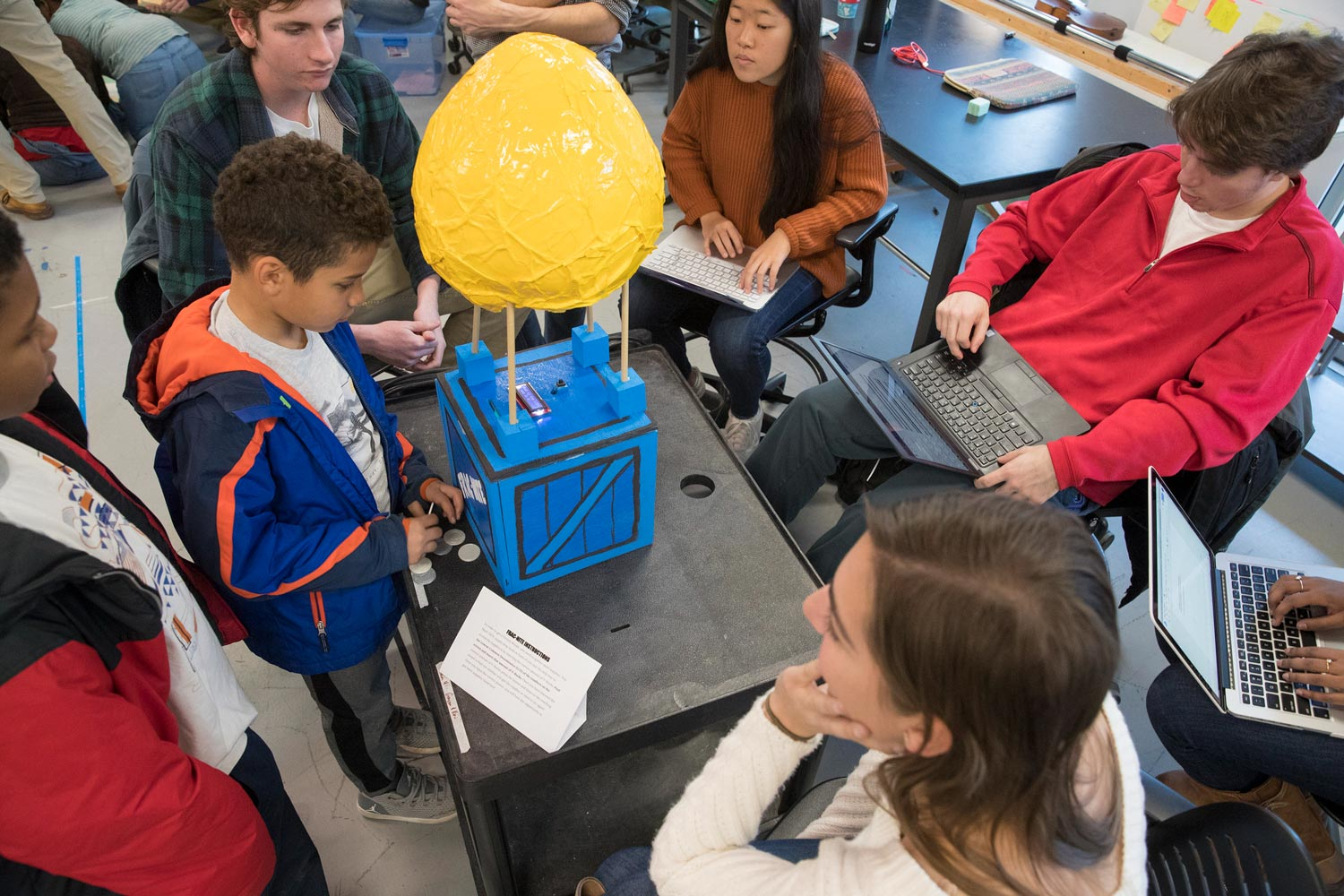 UVA students observe as Clark Elementary fourth-grade students find the common denominator and then insert coins in the box to determine the numerator.