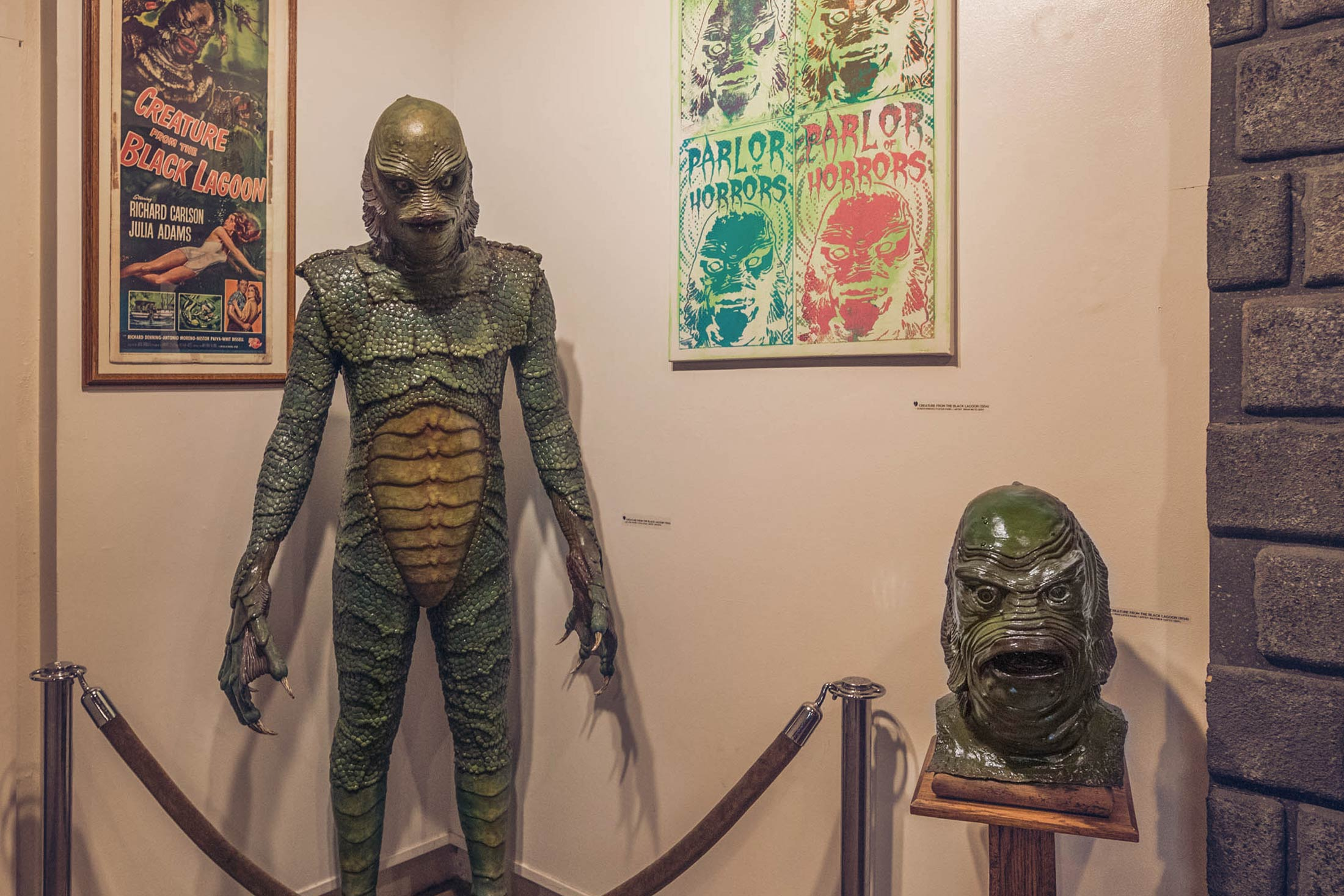 A life-sized gill-man model next to a gill-man mask on a pedestal