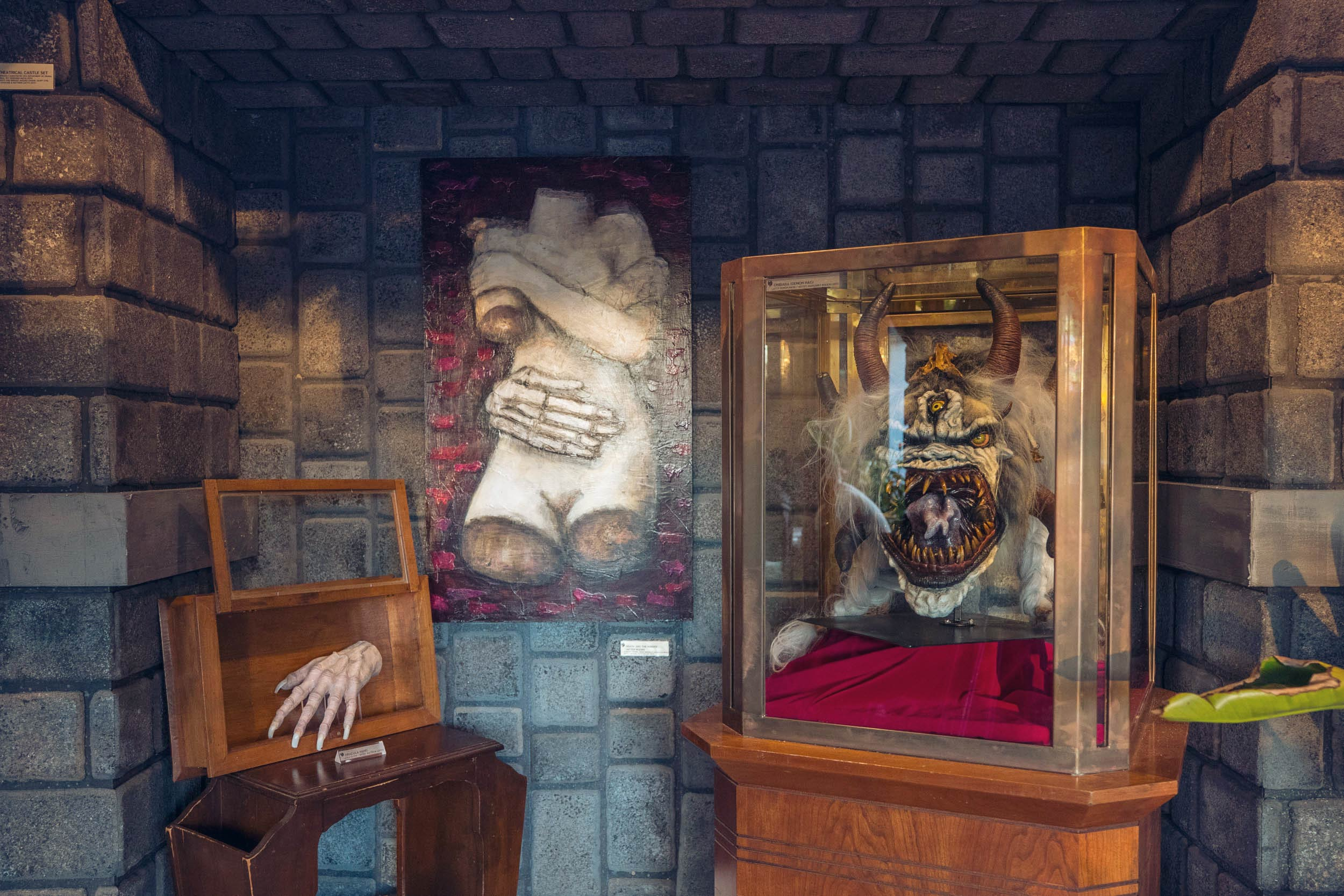 Horror-themed items on display in a room with fake stone walls