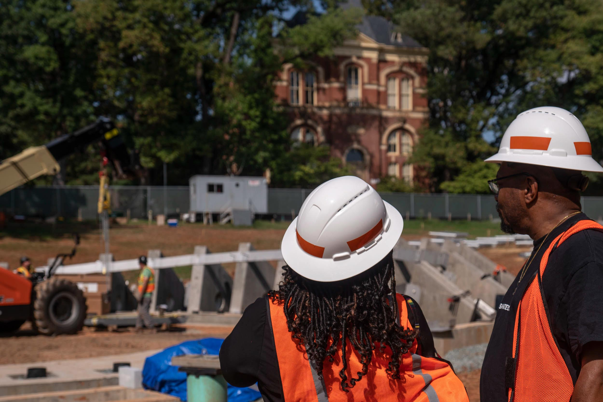 DeTeasa Gathers, a member of the Memorial to Enslaved Laborers Community Engagement Committee, and her husband Don Gathers watched the first stone of the memorial being hoisted into place on Wednesday. (Photo by Sanjay Suchak, University Communications)