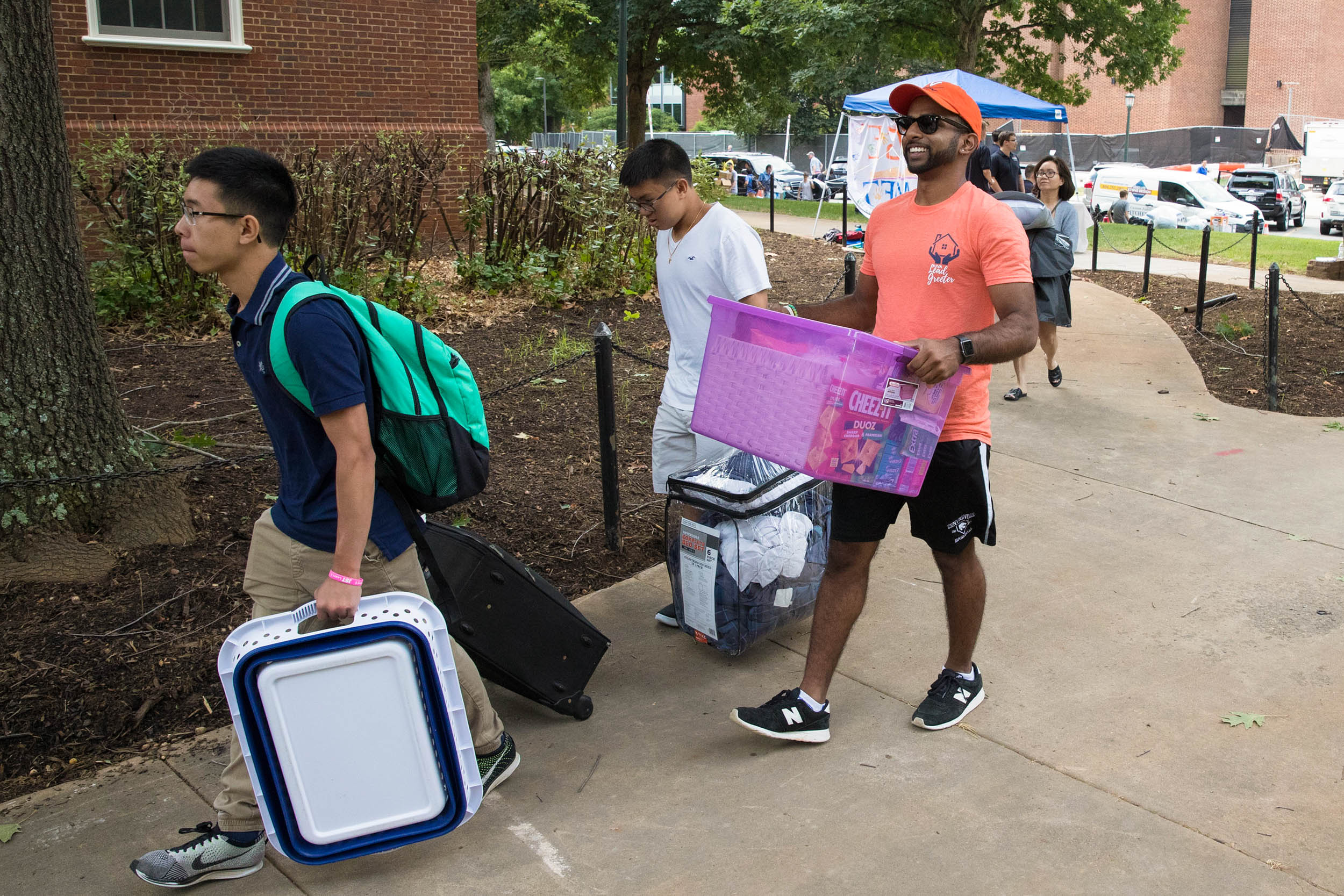 """Vinny Thota sports his orange """"Lead Greeter"""" T-shirt Friday, back for a second year to help families move their students into dorms."""