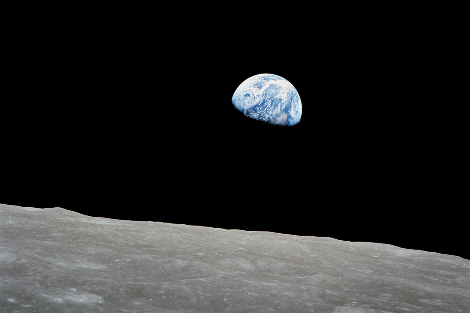 Photo of the Earth rising over the moon
