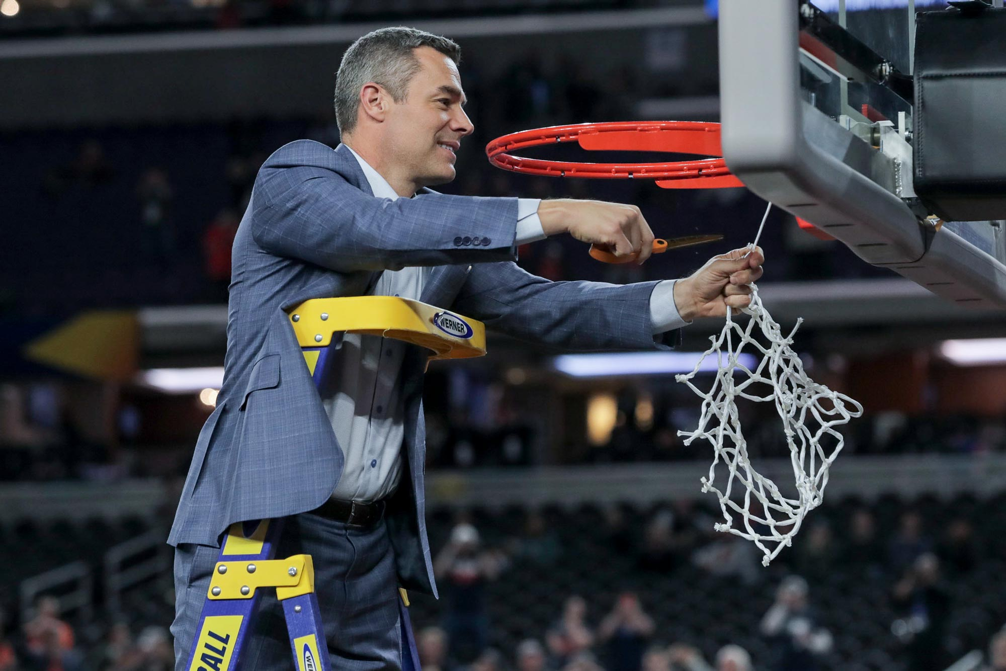 Head coach Tony Bennett cuts down the net at the Final Four, a cathartic moment for himself and the Cavalier basketball program.