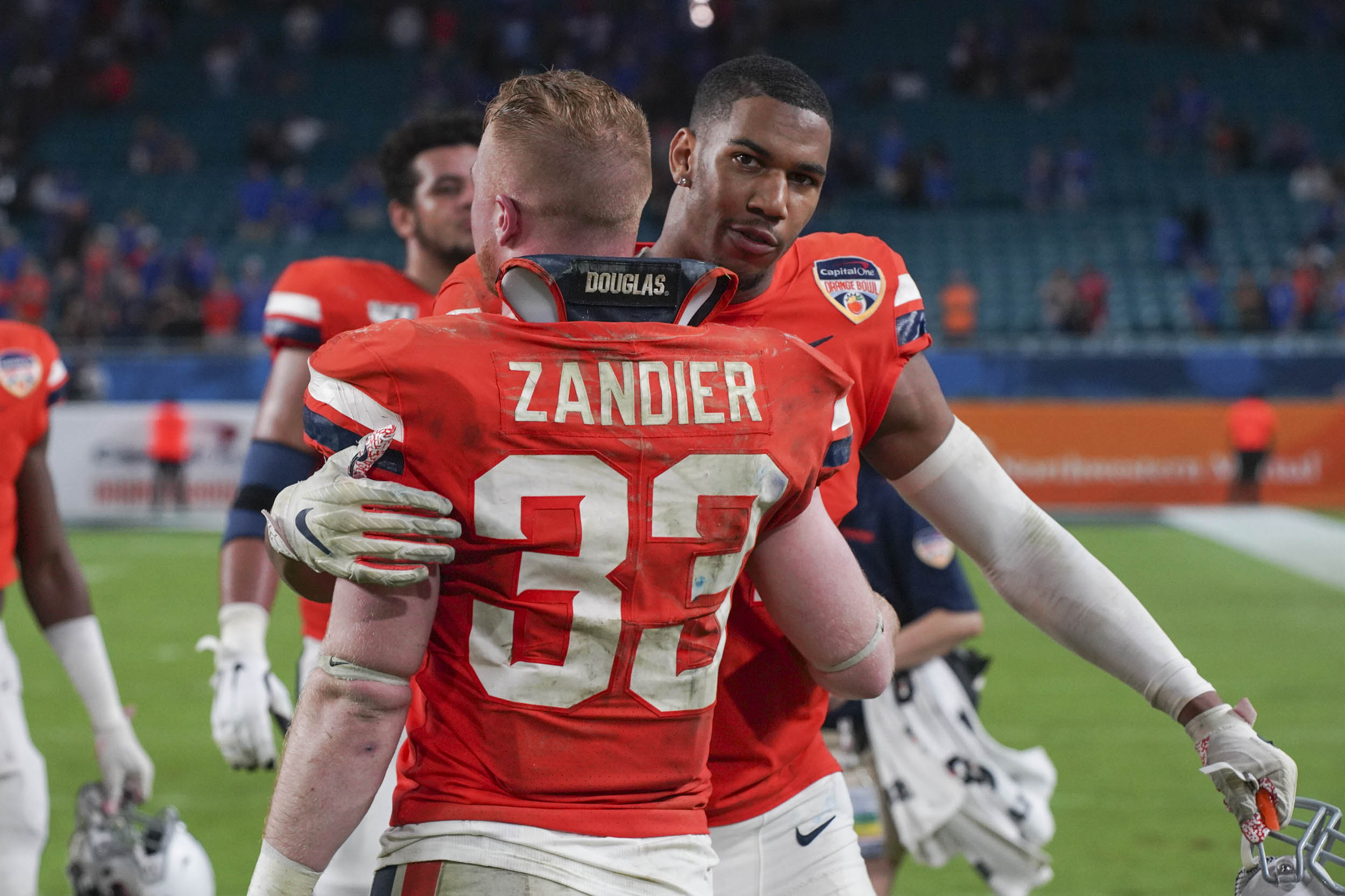 Zandier and teammate Charles Snowden share a hug after the game as the Hoos leave the field for the last time in 2019.