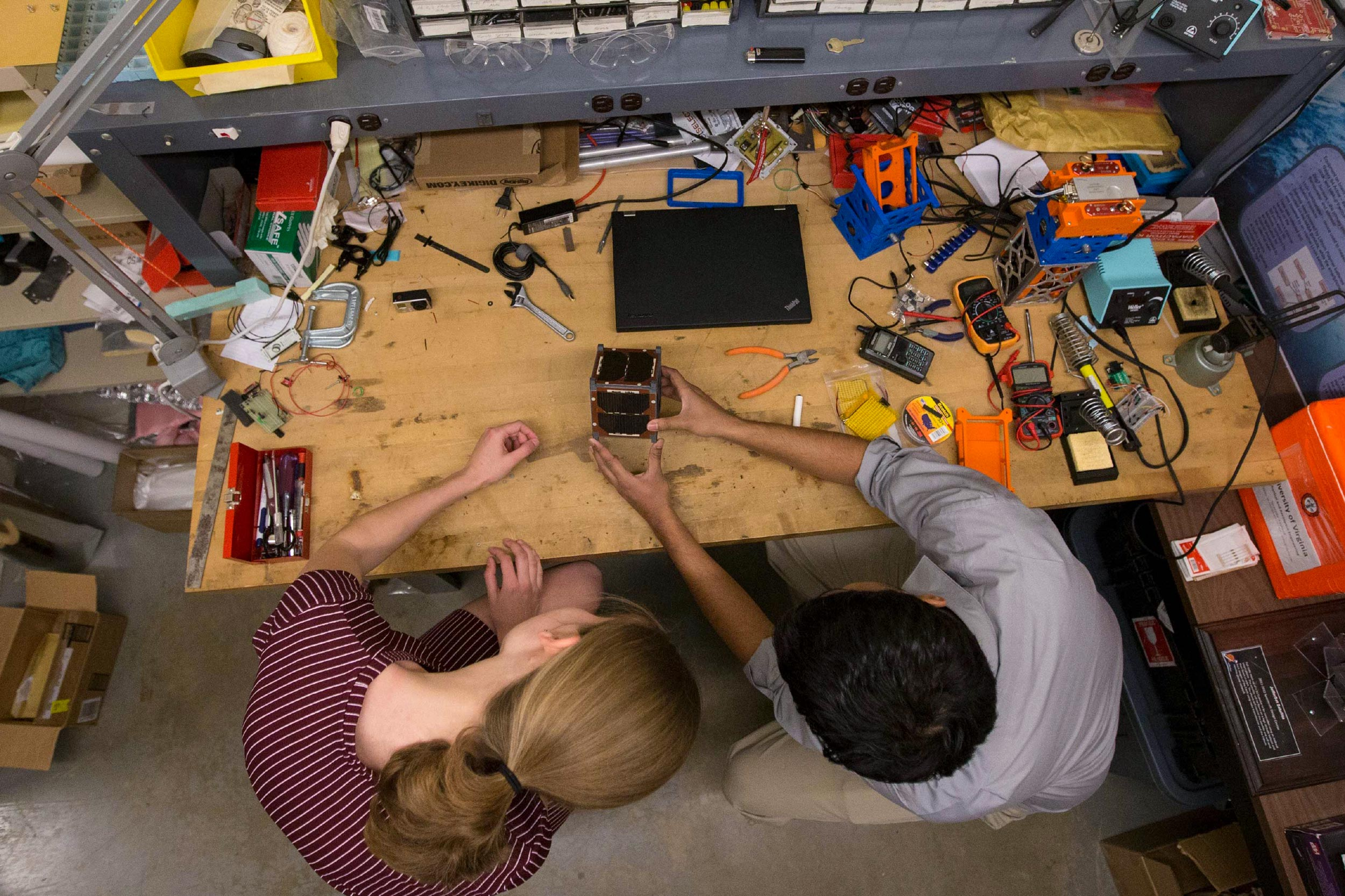 "Now-graduated UVA aerospace engineering students Robin Leiter, left, and Chandrakanth ""C.K."" Venigalla, work on an early iteration of UVA's CubeSat in 2016."