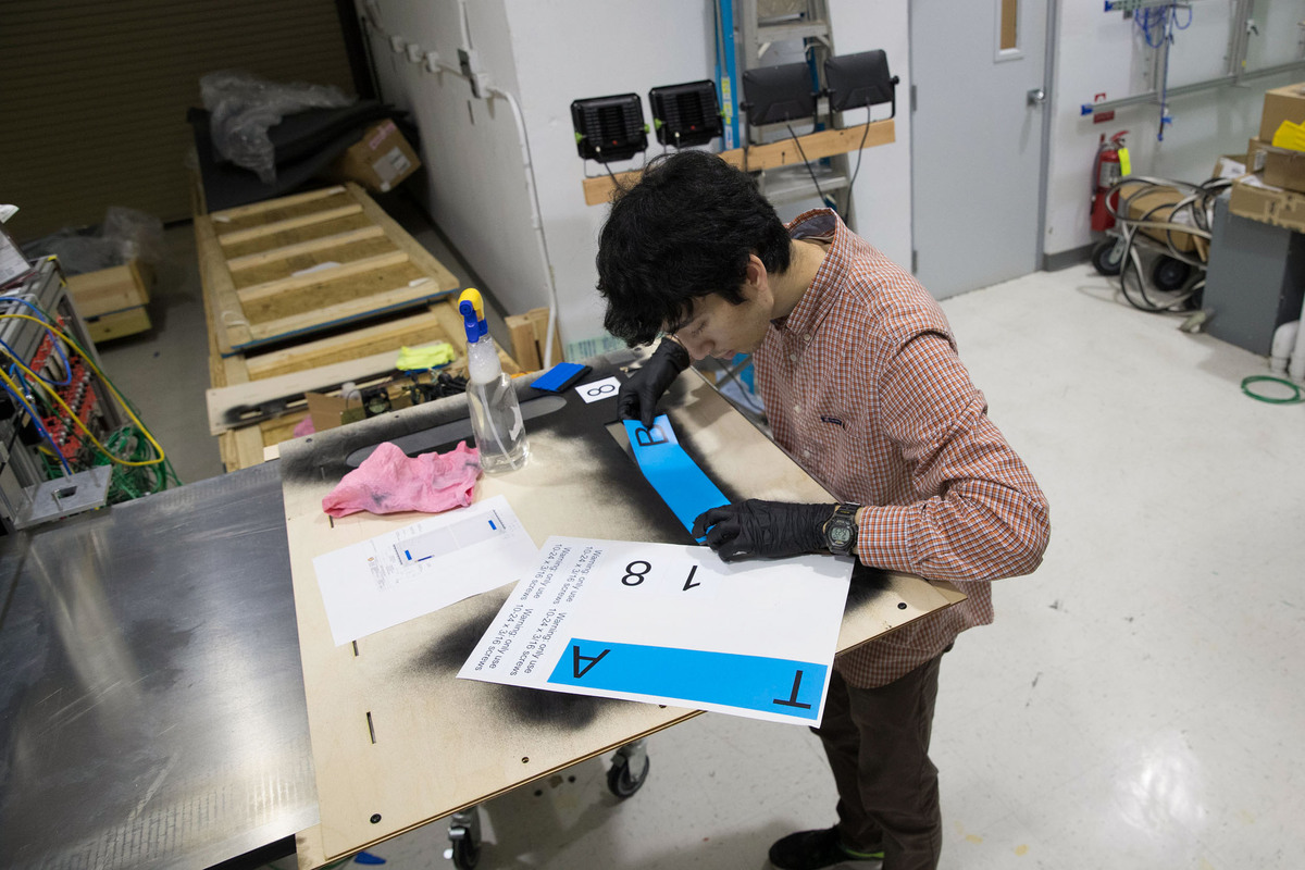 Student William Musk applies identification stickers to a completed module.