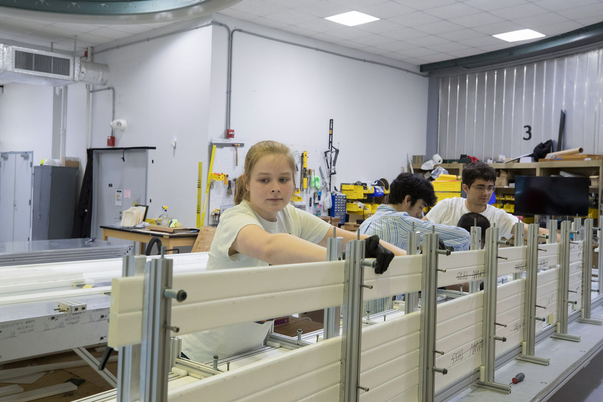 Physics students Hannah Woodward, left, William Musk, center, and Michael Stepniczka fabricate di-counters, the active detector components of a module.