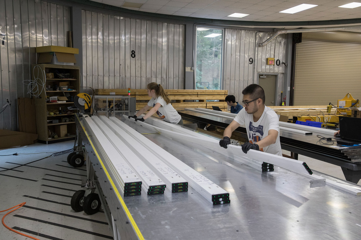 Students Hannah Woodward, William Musk (background) and Brian Tran, prepare to polish optical fibers so that more light will reach the photo detector when a muon passes through the di-counter. Particle_Detector_Fabrication_Part_A_16_DA.jpg – A diamond-tip