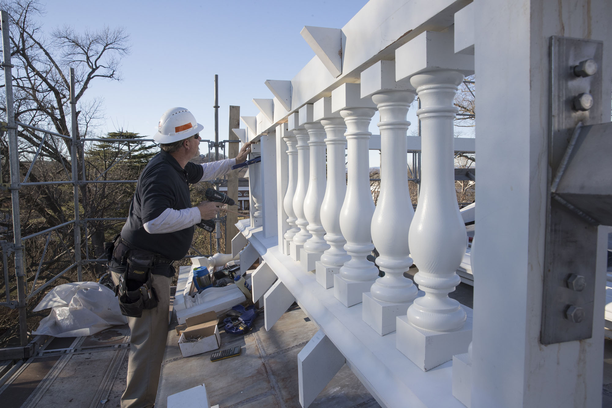 University workers install the new balustrade on the roof of Pavilon III, restoring its original appearance.