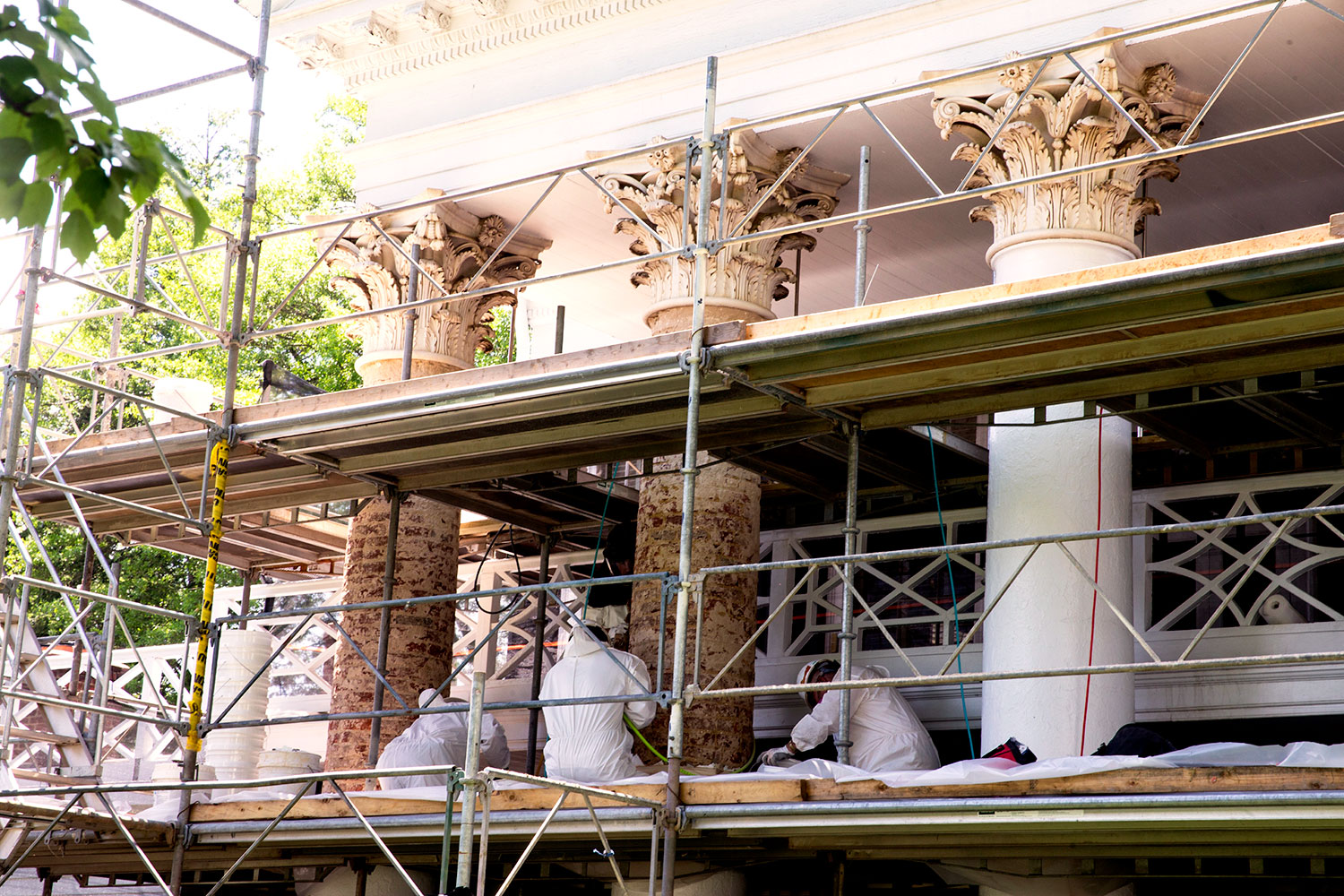 University masons strip the portland-cement stucco from the columns in front of Pavilion III.