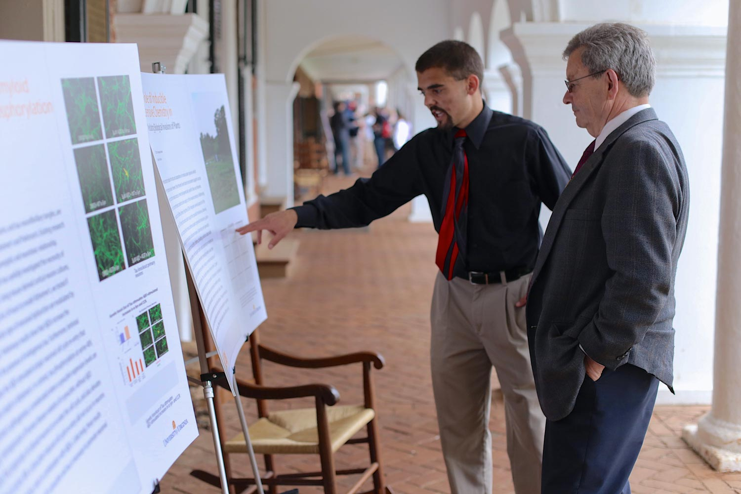 Phil Parrish, right, examining a research poster on display on the Lawn.