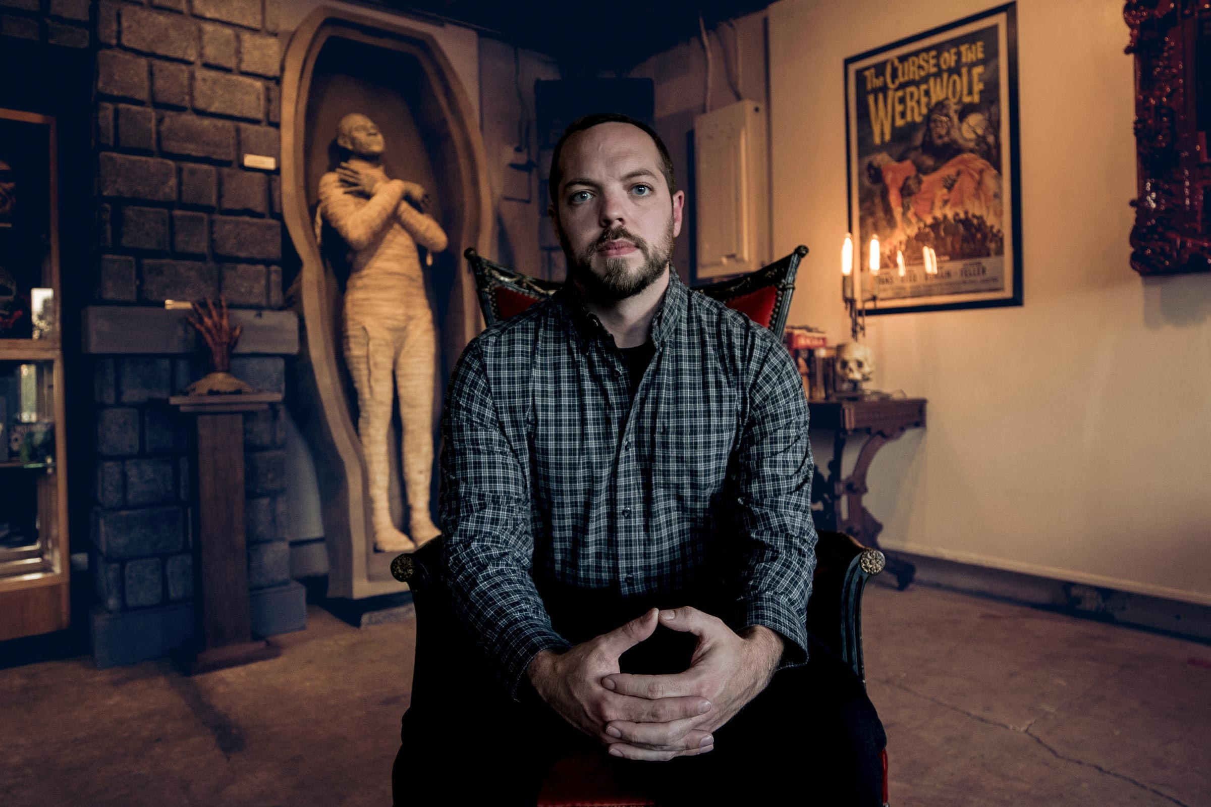 Portrait of a man in a chair in a horror-themed gallery