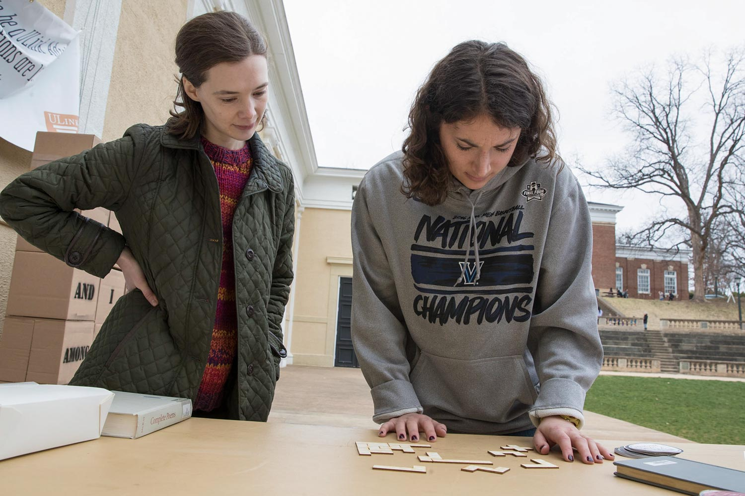 Jess Swoboda, a first-year graduate student in the English department, worked on a small version, made of cut wood, of the cardboard puzzle-poem, as Puzzle Poetry group member and English doctoral student Madeline Zehnder, left, looks on.