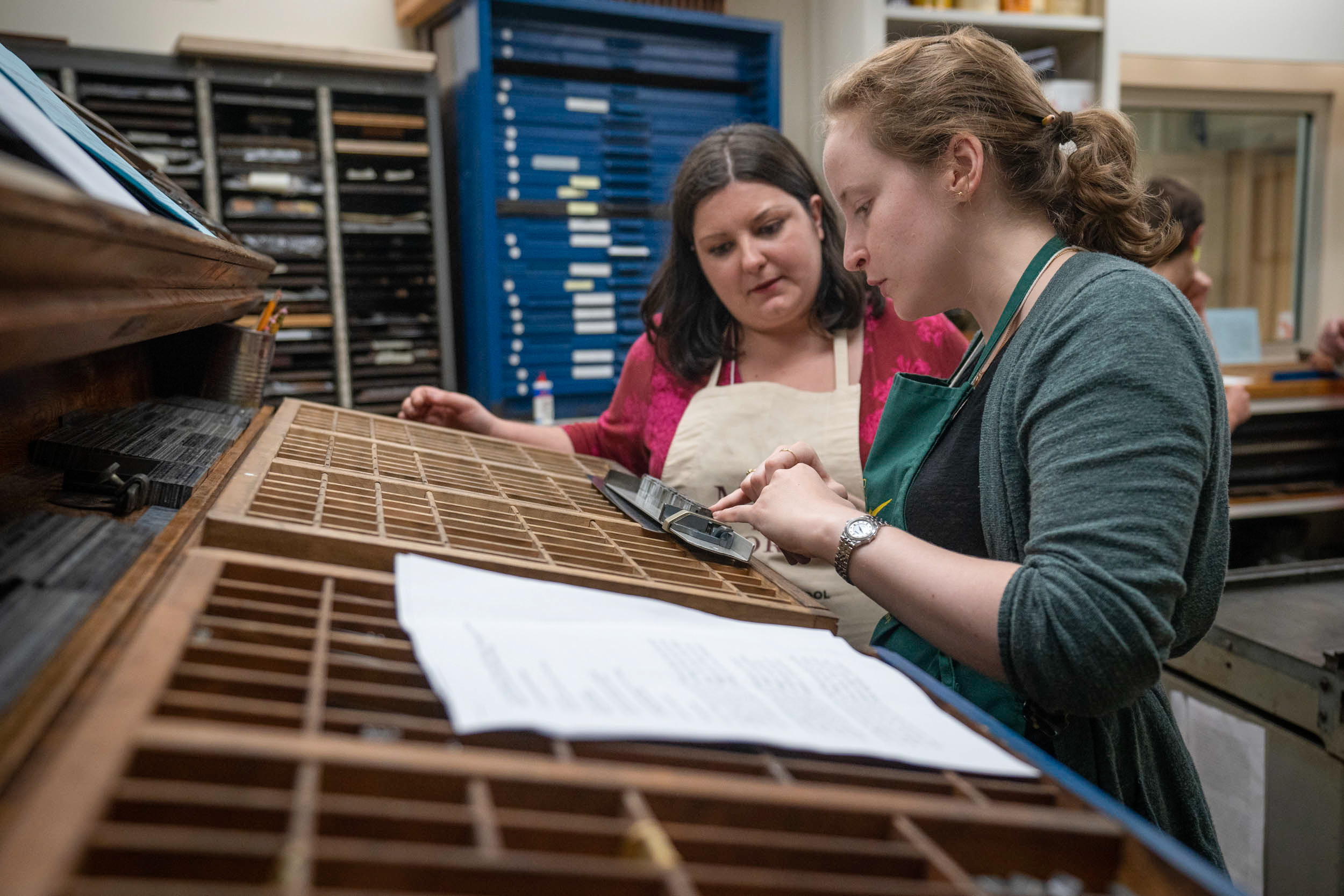 Course assistant Suzanne Glémot shows Amanda Rogus how the pieces of type fit together.